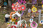 A man pauses at a gravesite decorated with flowers and wreaths for the Day of the Dead festival November 3, 2017 in Nuevo San Juan Parangaricutiro, Michoacan, Mexico.