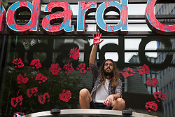 An environmental activist from Extinction Rebellion raises a hand after spreading blood-red paint across the facade of Standard Chartered bank during a Blood Money March through the City of London on 27th August 2021 in London, United Kingdom. Extinction Rebellion were intending to highlight the £23bn which they say Standard Chartered has invested in fossil fuels since the Paris Agreement whilst calling on the UK government to cease all new fossil fuel investment with immediate effect.