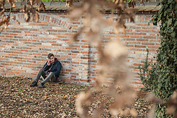 Young man talking on mobile phone and sitting on skateboard leaning against brick wall, Munich, Bavaria, Germany