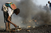 A boy rummages through ashes as he looks for strings of copper wire near the Agbogboloshie market in Accra, Ghana on Thursday August 21, 2008.