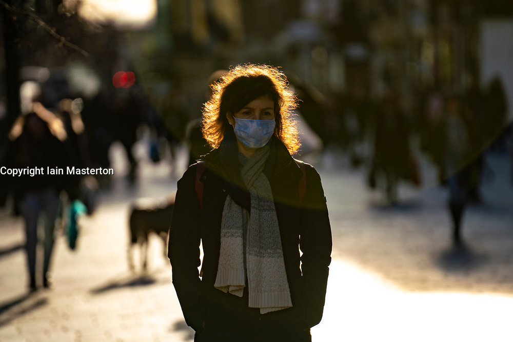 Glasgow, Scotland, UK. 19 November 2020. On the day before the highest level 4 lockdown is imposed on west and central Scotland, shops in Glasgow city centre and streets are busy with members of the public. Pictured; Backlit woman  in afternoon sunshine on Buchanan Street.  Iain Masterton/Alamy Live News