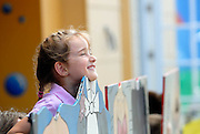 Child (6 years old) placing head onto cutout figure. Luna Park, Sydney, Australia