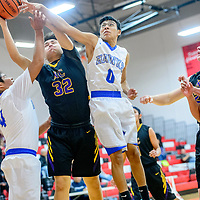 Laguna Acoma Hawks Lyle Bahe (4), left, and Jordan Day (0) vie for a rebound around Kirtland Central Bronco Jacoby Love (32) during the Eddie Peña Invitational basketball tournament in Grants Thursday.