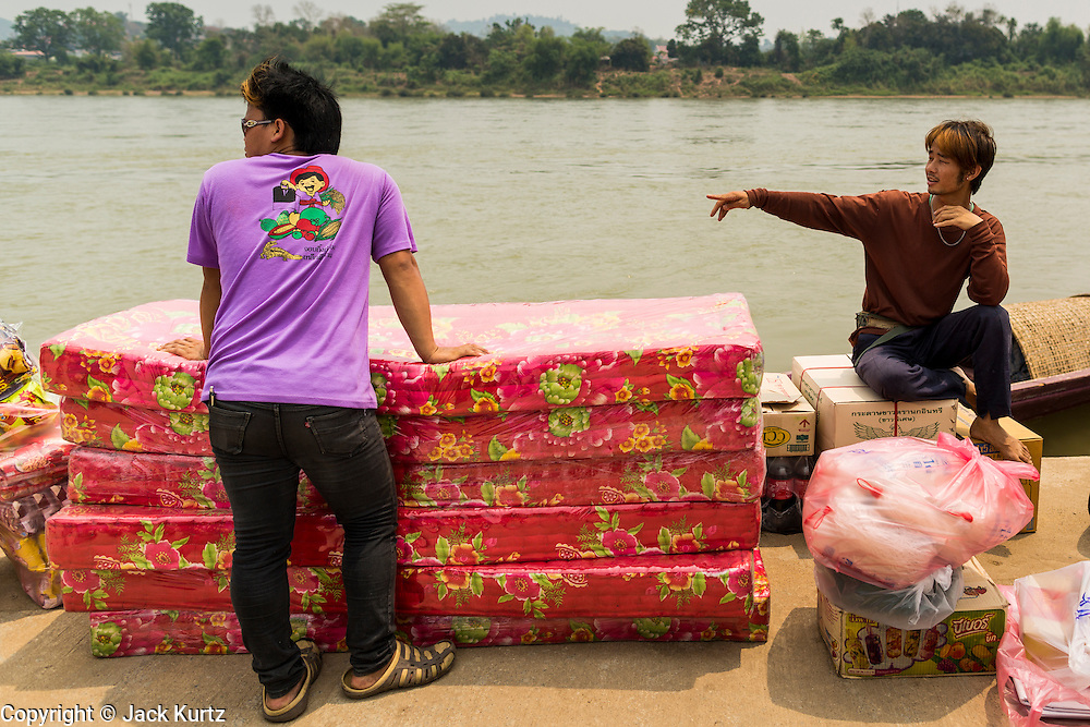 23 APRIL 2014 - CHIANG KHONG, CHIANG RAI, THAILAND: Men in Chiang Khong port wait for a small boat to take their load of Chinese made mattresses to across the Mekong River to Laos. Chiang Rai province in northern Thailand is facing a drought this year. The 2014 drought has been brought on by lower than normal dry season rains. At the same time, closing dams in Yunnan province of China has caused the level of the Mekong River to drop suddenly exposing rocks and sandbars in the normally navigable Mekong River. Changes in the Mekong's levels means commercial shipping can't progress past Chiang Saen. Dozens of ships are tied up in the port area along the city's waterfront.              PHOTO BY JACK KURTZ