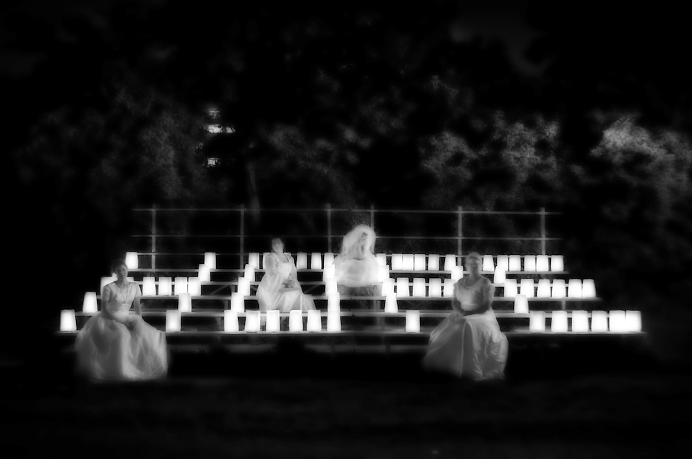 """Photographing for the Canadian Cancer Society's Relay for Life is a touching experience. There's an intangible quality surrounding the event. <br /> <br /> Picture the scene: an outdoor field, much like that of a school's outdoor field, with a quarter mile track around the circumference for track & field competition. Bleachers off to one side. A stage at the foot of the track. Several big-top tents scattered around the track, housing such things as registration, food, cancer survivors, massage therapy and more.<br /> <br /> On the entire inside circumference of the track are luminaries: specially designed paper bags with a lit candle inside. Each luminary is a tribute to the lives of loved ones who have been touched by cancer. The track can barely hold all of them.<br /> <br /> On the bleachers the word """"Hope"""" has been written with even more luminaries. Seventy-five luminaries for four letters. And indeed, there are many elements of Hope this evening. As well as another four-letter word: Love.<br /> <br /> In Canada alone, two in five people face a diagnosis of cancer in their lifetime. It is more critical than ever to raise awareness about the disease and the impact it has on the lives of people.<br /> <br /> Photographer Dean Oros  created the """"Angelic"""" series of midnight images using candle light and long exposures while photographing the CCS Relay for Life. Models are from the The Brides' Project, which donates a portion of its wedding gown sales to cancer research.<br /> <br /> Click on thumbnails to view captioned, full-size images. Select images are available to purchase for personal and commercial use."""
