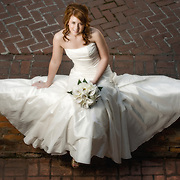 A bride poses for her bridal portrait on a brick wall at Millstone at Adam's Pond, a wedding venue in Columbia, S.C. ©Travis Bell Photography