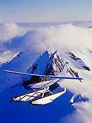 Wings of Alaska Cessna 206 flying over nunataks of the Coast Range rising above the Juneau Icefield, Tongass National Forest, Alaska.