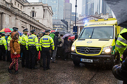 London, UK. 14 October, 2019. Climate activists from Extinction Rebellion move aside to allow an ambulance to pass through the busy junction in front of the Bank of England which they had occupied at 7am on the eighth day of International Rebellion protests. Large numbers of police had arrived shortly before in order to attempt to clear the junction.
