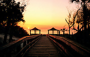 A view of the sunset from a wooden walkway that leads to the ocean