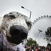 Aurora by the London Eye and Shell London HQ.The giant polar bear puppet Aurora made by Greenpeace walked the streets of London in defence of the Arctic as part of a Greenpeace global day of action. The parade,part performance part protest, was to highlight the melting ice caps and the increasing and potentially devastating oil drilling in the arctic sea. Shell is one of the companies drilling and the march through London ended up outside Shell London HQ to draw attention to their oil business in the arctic. Aurora, the biggest polar bear in the world represents all endangered species in arctic.