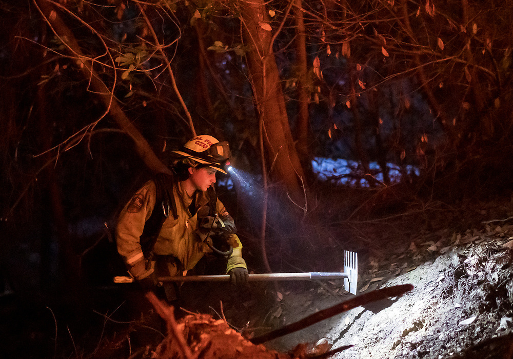 Cal Fire firefighter Bianca Romeo cuts a fire line to help protect a home from the CZU Lightning Complex fire rages near Ben Lomond, Calif. on Aug. 20, 2020.
