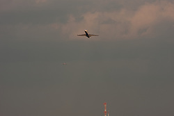 A plane takes off as a flock of birds flies in front of it.  Another plane in the background lands.