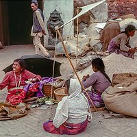 A woman spins wool and she and other women sell their wares in the bazaar at Kathmandu, Nepal.