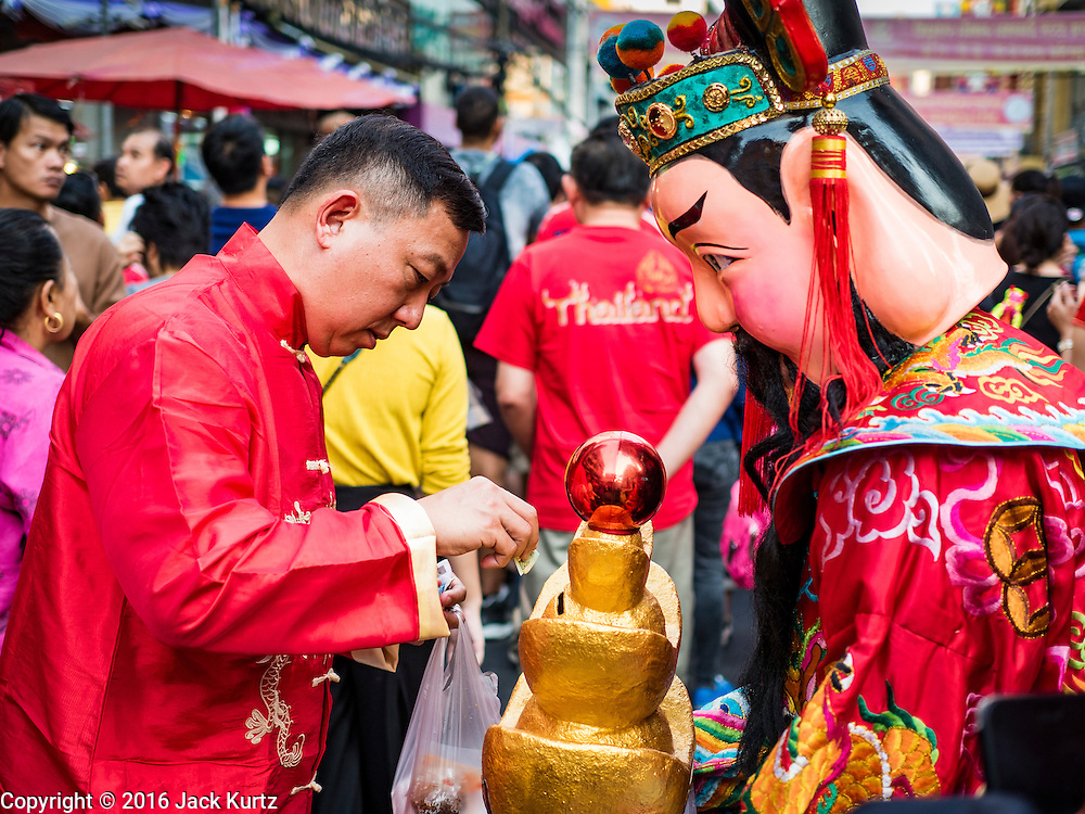 "08 FEBRUARY 2016 - BANGKOK, THAILAND: A man makes an offering to a Taoist deity during the Chinese New Year parade in Bangkok's Chinatown district during the celebration of the Lunar New Year. Chinese New Year is also called Lunar New Year or Tet (in Vietnamese communities). This year is the ""Year of the Monkey."" Thailand has the largest overseas Chinese population in the world; about 14 percent of Thais are of Chinese ancestry and some Chinese holidays, especially Chinese New Year, are widely celebrated in Thailand.       PHOTO BY JACK KURTZ"