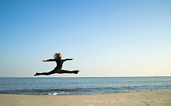Young woman jumping gracefully on the beach