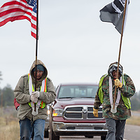 Carrying the US and POW flags, Pete Tsinnijinnie, of Chinle and Larry Ashkie, of Pinon, walk together along AZ-264, during the veterans walk to the Navajo Nation Council Chambers in Window Rock on Wednesday.