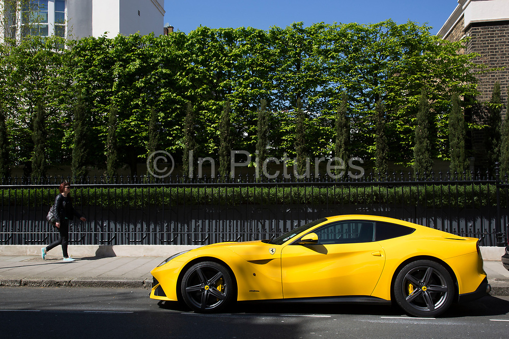 Yellow Ferrari supercar parked in front of a well kept hedge in Chapel Street in Belgravia, one of the most exclusive areas in central London. In a selected few boroughs of West London, wealth has changed over the last couple of decades. Traditionally wealthy parts of town, have developed into new affluent playgrounds of the super rich. With influxes of foreign money in particular from the Middle-East. The UK capital is home to more multimillionaires than any other city in the world according to recent figures. Boasting a staggering 4,224 'ultra-high net worth' residents - people with a net worth of more than $30million, or £19.2million.. London, England, UK.