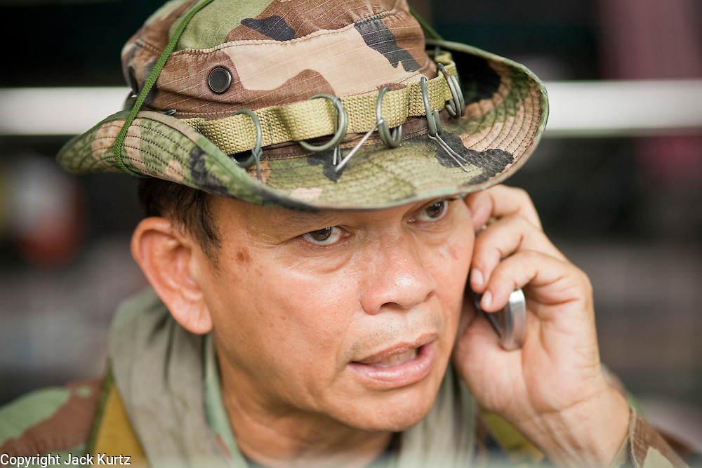 """May 12 - BANGKOK, THAILAND: Maj. Gen. KHATTIYA """"Seh Daeng"""" SAWASDIPOL uses a cell phone to stay in touch with Red Shirt barricades in the Red Shirt camp in Bangkok Wednesday. Seh Daeng, as he is known, has emerged as the Red Shirts unofficial military commander. He has organized the barricades that ring the Red Shirt camp and has threatened to organize a guerilla campaign against the government if the Red Shirt protest is crushed by force. Seh Daeng is a hero to many Thais because he is credited with crushing Thailand's communist insurgency in the 1970's and 80's. He was the commander of Thailand's Internal Security Operations Command but after his political activities became apparent he was made the head aerobics instructor for the Thai army. He is now seen as one of the major personalities destabilizing the country and the government alleges that he is behind many of the grenade attacks and drive by shootings directed at government buildings and officials and he is wanted for a long list of felony offenses including weapons charges and terrorism related charges. Although some Red Shirts have officially repudiated him, he is still frequently seen around the Reds' barricades. The army has started proceedings to fire him, but he remains a general on active duty.   Photo by Jack Kurtz"""