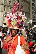 A woman in an elaborate hat, with sprays of flowers and an inverted basket.