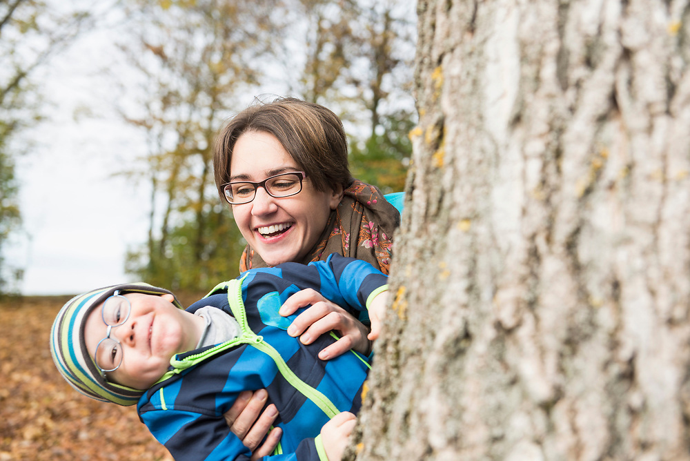 Mother and son peeking from big tree and laughing in autumn scenery