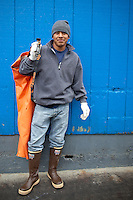 Fish worker Ricardo Francisco, stands in front of the blue wall of one of the fish processing plants in downtown Newport, Oregon.