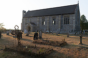 Evening sunlight falls across the churchyard of St Nicholas church, Dilham, on 11th August 2020, in Dilham, Norfolk, England.