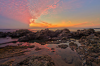 A colorful sunset fills the sky over the Pacific Ocean. This was taken at Crystal Cove State Park in California during low tide. Many of the tide pools were exposed and hermit crabs, anemones and other sea creatures could be seen. Both low and high tide usually occur twice a day approximately 6 hours apart. During a quarter moon, when the moon is at a right angle with the earth and the sun there is less variation between high and low tides. This is called a neap tide. But when there is a full moon or a new moon the tides are especially high and low. The gravitational force of the sun and the moon combine to generate more of a pull on earth's oceans. This is called a spring tide.