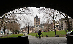 "Cologne, Germany, Jan. 2012 -  Pedestrians, framed by the arches of the Hohenzollern bridge, make their way along the Rhein River Promenade, in the shadow of the Great St. Martin's church, in the ""Old Town"" district of Cologne, Germany. (Photo © Jock Fistick)."