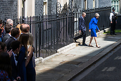 London, UK. 24 July, 2019. Theresa May, accompanied by her husband Philip and watched by her staff, leaves 10 Downing Street to address the nation before proceeding to Buckingham Palace to tender her resignation to the Queen.