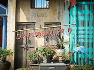 Sausages hanging on a bamboo stick are left to dry in the sunshine in front of an old house facade, Vietnam, Southeast Asia