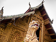 24 JUNE 2011 - CHIANG MAI, THAILAND: The Bot, or ordination hall, at Wat Mahawan in Chiang Mai, Thailand is guarded by Temple Dragon. PHOTO BY JACK KURTZ