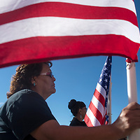 Judy Platero, family friend from Thoreau, NM, holds an American flag in a line to greet the body of fallen Navajo Nation police officer Houston Largo for his funeral service at Rehoboth Christian School in Gallup Thursday March 16.