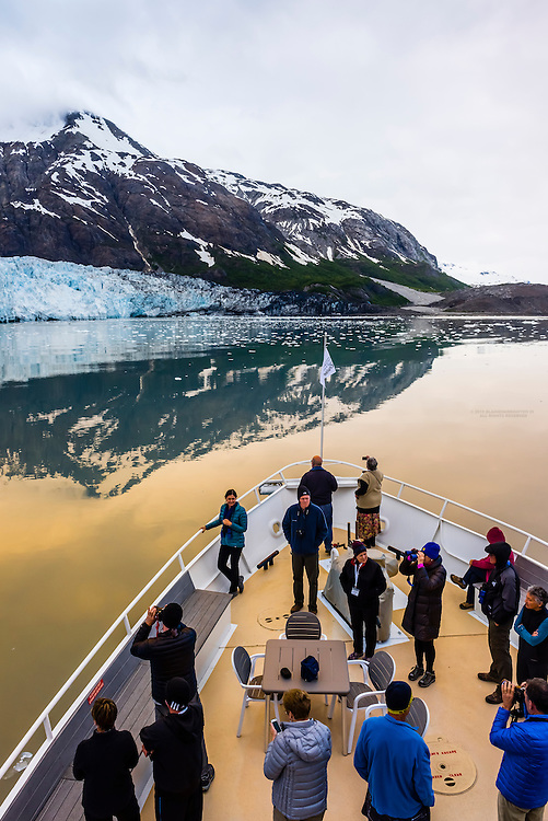 """Passengers aboard the Un-Cruise  """"Wilderness Explorer"""" view the Margerie Glacier from the bow of the boat, Glacier Bay National Park, southeast Alaska USA."""