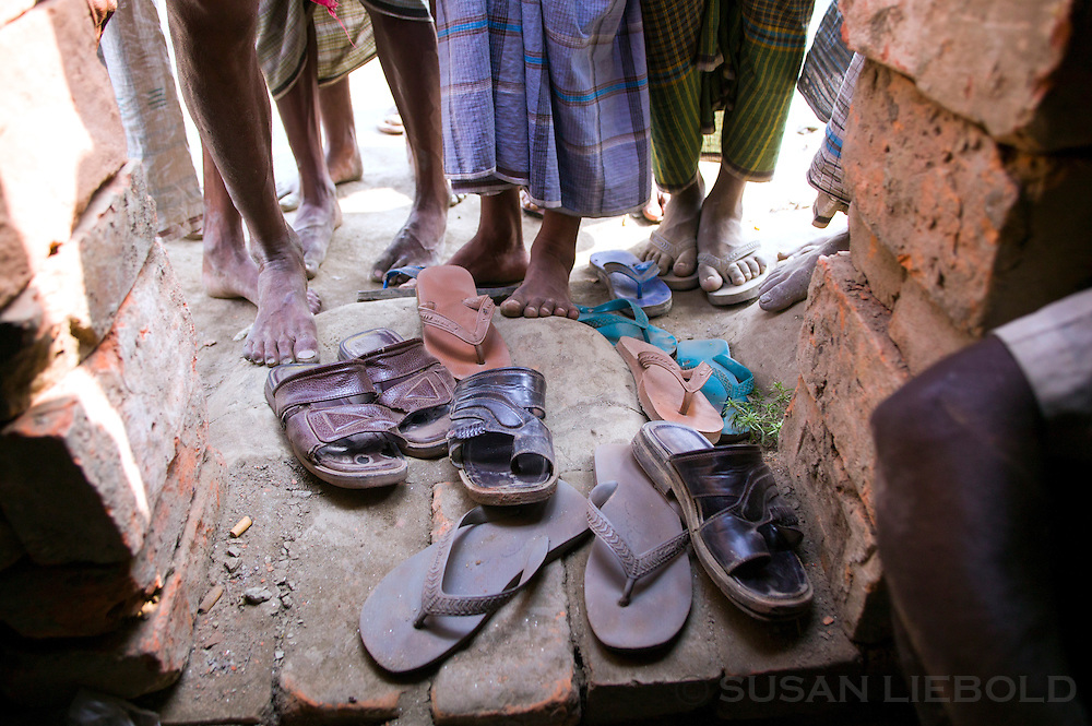 Men at a brick making factory in Bangladesh take off their shoes and leave them at the entrance of their makeshift lodging during the brick making season.