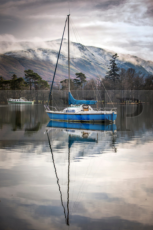 © Licensed to London News Pictures. 13/02/2020. Glenridding UK. Boats reflect in to the calm water of Ullswater lake in Glenridding today in Cumbria as the UK braces for more bad weather over the weekend. Photo credit: Andrew McCaren/LNP