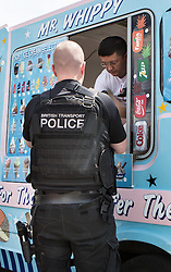 © Licensed to London News Pictures. 18/07/2015. London, UK. Armed police officers park illegally on double yellow lines using their emergency lights to buy ice cream on a warm summers day. Photo credit : James Gourley/LNP