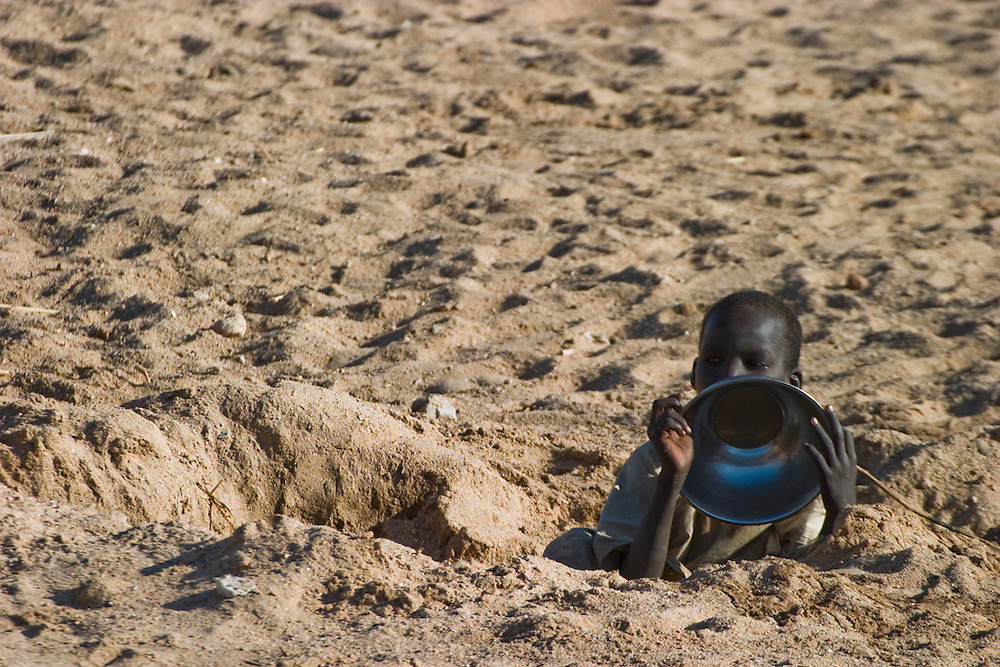 A boy digs for water from a nearly dry riverbed (called a wadi) in the Breidjing Refugee Camp in Eastern Chad. Water is a constant preoccupation in the Breidjing Refugee Camp, home to 30,000 refugees from Darfur, Sudan. Every day, lines of women and children carry jugs and pots of drinking and cooking water from distribution points to their tents. To get extra water to wash clothes, families dig pits in nearby wadis (seasonal river beds), creating shallow pools from which they scoop out water. in the month of November, the camp wadi had water three feet below the surface. As the dry season advances, the sand pits get deeper and deeper.