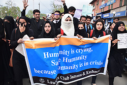 April 18, 2018 - Srinagar, Jammu & Kashmir, India - Kashmiri locals and students hold placards during demonstration held in Srinagar summer capital of Indian Kashmir and shouts anti Indian Slogans seeks justice for minor Kathua girl who was raped repeatedly in Temple.  .Local and students across Srinagar city continues to took to the streets of Srinagar Summer Capital Of Indian Kashmir during the demonstration against the rape and murder of 8 year old minor girl, seeking justice. Reported erupted outside many colleges between students and Police personal. Police used tear smoke shells and water canon to disperse the college students protestors..Victim, An eight year old girl belonged to a shepherd Bakerwal family. On January 10, she went missing and her body was found a week later laying in the nearby forest of Ranjana In Kathua Jammu. The poor girl was gangraped for seven days in ''Devisithan'' temple in Kathua Jammu. (Credit Image: © Abbas Idrees/SOPA Images via ZUMA Wire)