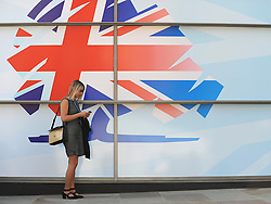 © Licensed to London News Pictures. 03/10/2011. MANCHESTER. UK. A woman uses her mobile phone in front of a hoarding bearing the Conservative Party Logo at The Conservative Party Conference at Manchester Central today, October 3, 2011. Photo credit:  Stephen Simpson/LNP