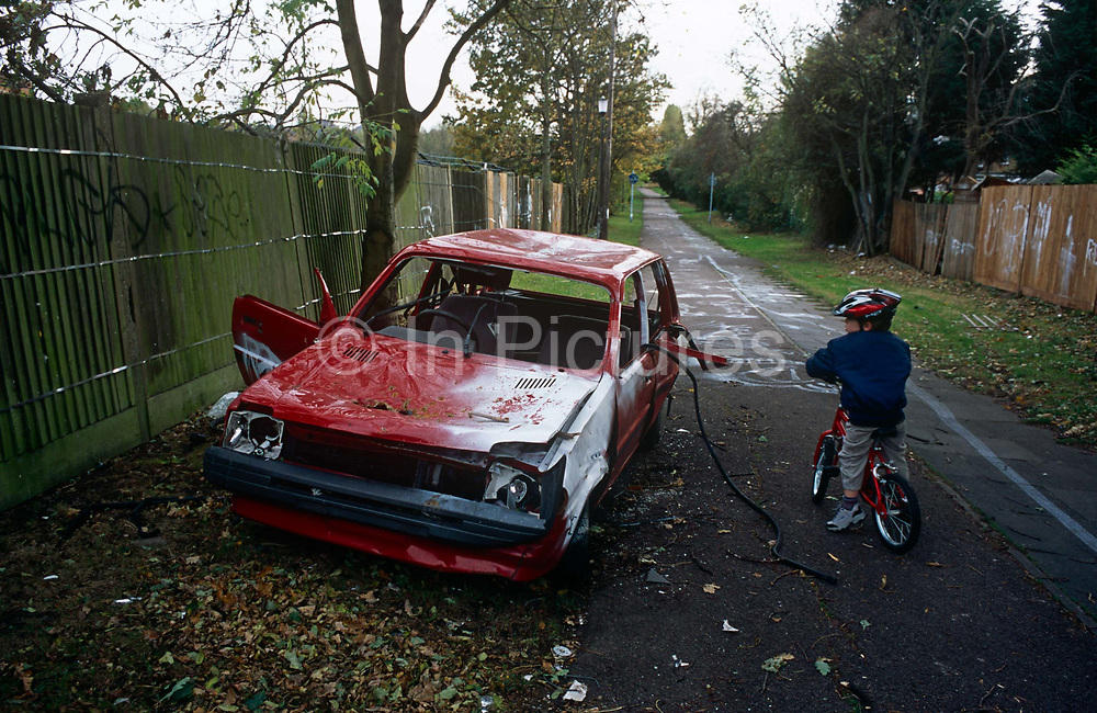 A 5 year-old boy has his bike journey to nursery school disrupted by a vandalised car that lies on the side of a quiet path in Dulwich, south London. Perhaps stolen and certainly attacked then left on the side of this pedestrian thoroughfare where graffiti has been sprayed on the pavement and fences that back on to nearby homes. The alleyway is used by cyclists and commuters taking a quiet route into central London from this leafy suburb.