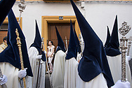 A girl watches a Holy Week procession passing by a narrow street in the centre of Cordoba, Andalusia. Spain