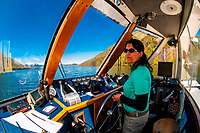 Captain Dawn Rauwolf steering the tour boat Kalinin in Misty Fjords National Monument, near Ketchikan, southeast Alaska, USA