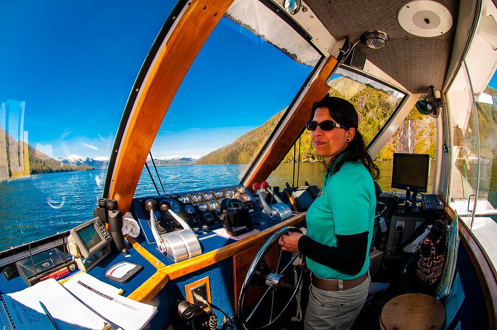 Captain Dawn Rauwolf steering the tour boat Kalinin in Misty Fjords National Monument, near Ketchikan, southeast Alaska, USA