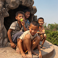 """Boys sitting near a giant pumpkin statue's exit, which ends and the top of the statue. Seen in """"Xieng Khouan"""" Buddha Park."""