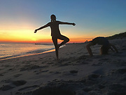 Children do acrobatics and ti chi on beach at sunset, Cape May