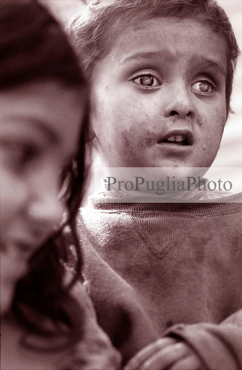A Kashmiri holds her youngest brother in a 'long established' refugees camp. The latter has been blind since birth. ..Jelum Valley 2001