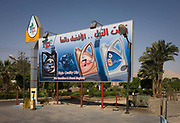 A modern billboard sign in Arabic advertising engine oils in the village of Bairat on the West Bank of Luxor, Nile Valley, Egypt. The clean noticeboard contrasts with its dirtier surroundings which are dusty and less developed.