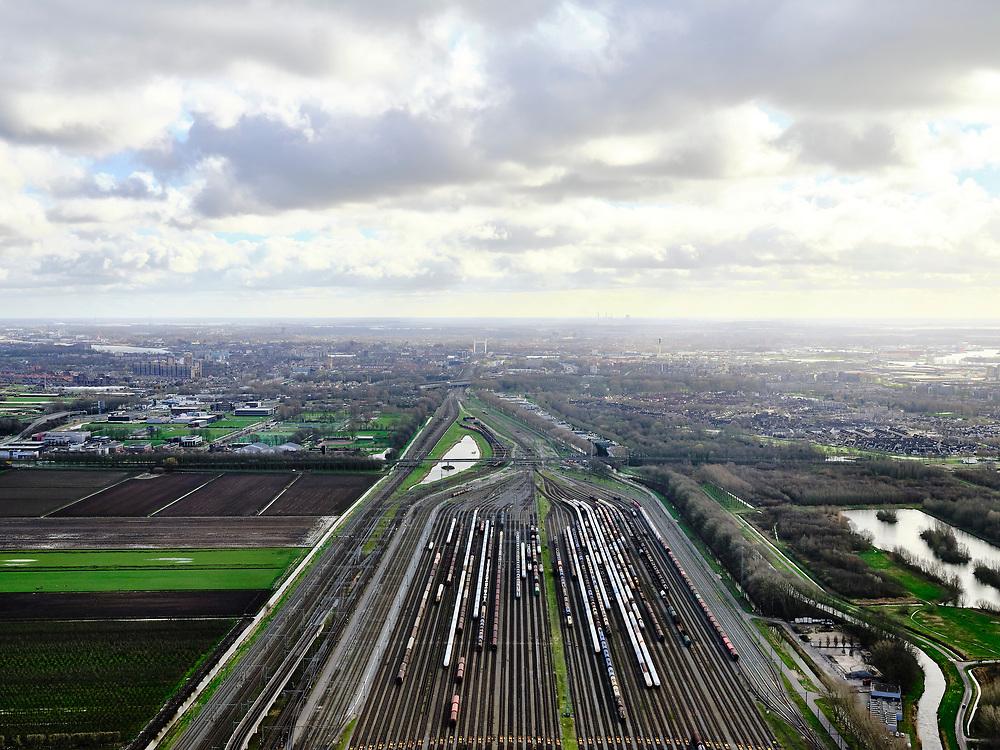 Nederland, Zuid-Holland, Zwijndrecht, 25-02-2020; Kijfhoek, rangeerterrein voor goederentreinen. Overzicht van de verdeelsporen (richting Dordrecht). Kijfhoek huisvest Keyrail, exploitant Betuweroute en is in beheer bij ProRail. De Betuweroute, die begint als Havenspoorlijn op de Maasvlakte, verbindt via Kijfhoek de Rotterdamse haven met het achterland. Het rangeeremplacement dient voor het sorteren van goederenwagons waarbij gebruik gemaakt wordt van de zwaartekracht, het 'heuvelen': de wagons worden de heuvel opgeduwd, bij het de heuvel afrollen komen ze, door middel van wissels, op verschillende verdeelsporen. Railremmen zorgen voor het automatisch remmen van de wagons. Na het heuvelproces staan de nieuw samengestelde treinen op aparte opstelsporen.<br /> Kijfhoek, railway yard (train shunting-yard) used by ProRail and Keyrail (Betuweroute operator). Kijfhoek connects via the Betuweroute (beginning as Havenspoorlijn on the Maasvlakte), through the port of Rotterdam with the hinterland. The shunting yard for sorting wagons makes use of gravity. The new trains are assembled on separate tracks.<br /> luchtfoto (toeslag op standard tarieven);<br /> aerial photo (additional fee required)<br /> copyright © 2020 foto/photo Siebe Swart