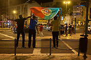 Portuguese football fans celebrate their countrys victory over France in the Euro 2016 tournament final on 10th July 2016, in Lisbon, Portugal. Waving their national flag above their heads, they wave to passers-by after the final whistle in the game that captivated Portugal with their hero, Christiano Ronaldo the symbol of their well-being and patriotism.
