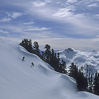 Skiers descend Shukson Arm in the Mount Baker Wilderness near Washington's Mount Baker Ski Area.
